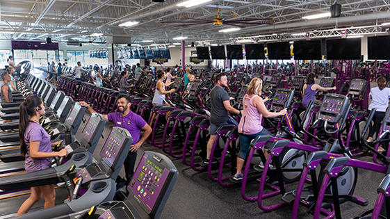 Planet Fitness members working out in a clean, spacious facility