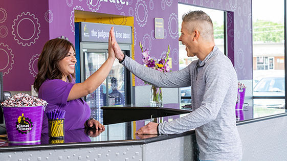 friendly Planet Fitness team member greeting a member with a high five